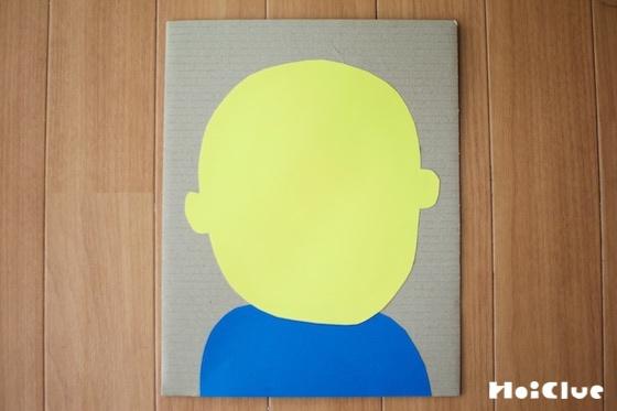 ダンボールに顔の形に切った画用紙を貼り付けた写真